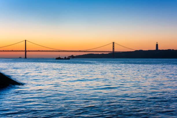 april 25th bridge and christ the king statue in lisbon portugal at sunrise - cristo rei lisboa imagens e fotografias de stock