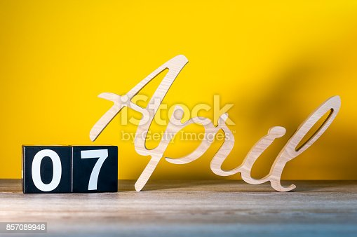 istock April 7th. Day 7 of month, calendar on wooden table and green background. Spring time, empty space for text 857089946