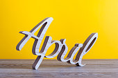istock April - carved text of wooden at light yellow background. Second spring month 660275440