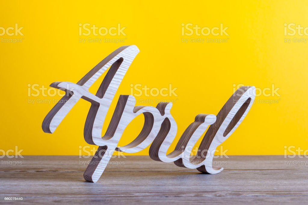 April - carved text of wooden at light yellow background. Second spring month stock photo