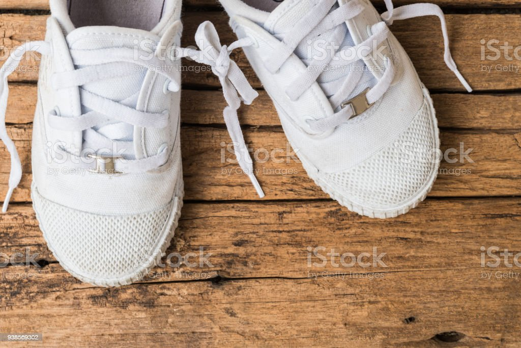 April fool's day concept. shoelaces tied together on wooden background. stock photo