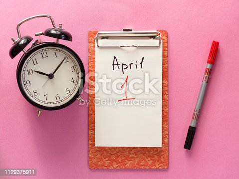 1 april fool's day, notebook, clock, pen. Flat lay on a pink background.