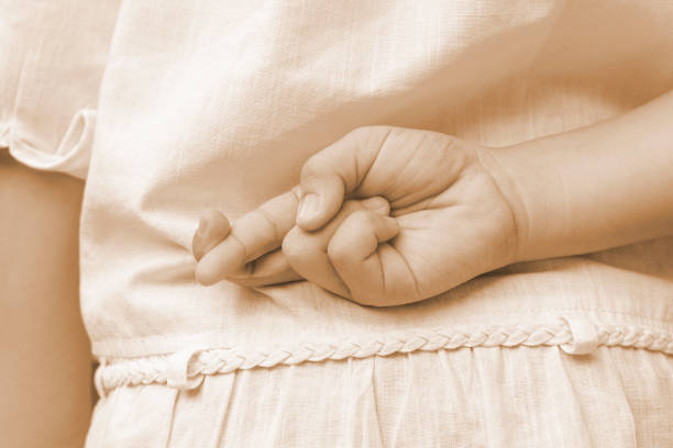 april fools ' day.close up of female kidhand crossing fingers behind her back. girl child es index finger und mittelfinger kreuzen sich, lügen und betrügen konzept in sepia vintage-ton. - wahre lügen stock-fotos und bilder