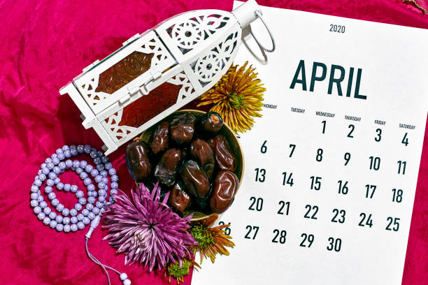 April monthly calendar on red April monthly calendar on the red silk textile background. Islamic Ramadan Eid festive background with rosary beads, lantern and dates fruits muziekfestival stock pictures, royalty-free photos & images