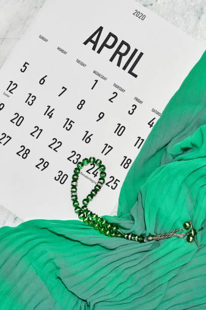 April monthly calendar April monthly calendar on green silk textile background. Islamic Ramadan Eid festive background with Islamic praying rosary beads muziekfestival stock pictures, royalty-free photos & images