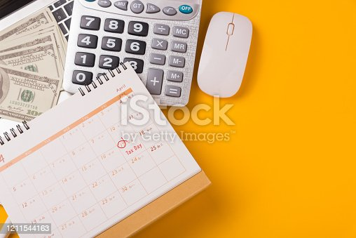 1185240988 istock photo April of the year is Tax Day, Top view flat lay closeup calculator, laptop computer, calendar, and Dollar money, on yellow background business finance budget concept 1211544163