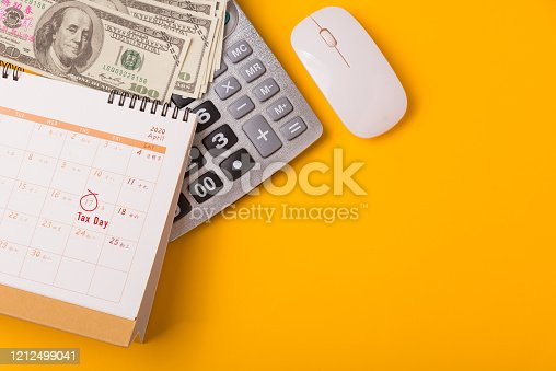 1185240988 istock photo April of the year is Tax Day, Top view flat lay closeup calculator, laptop computer, calendar, and Dollar money, on yellow background business finance budget concept 1212499041