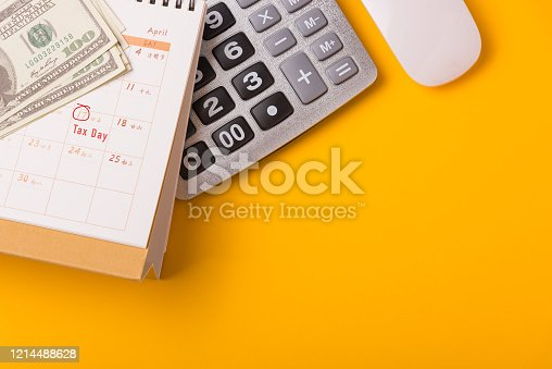 1185240988 istock photo April of the year is Tax Day, Top view flat lay closeup calculator, laptop computer, calendar, and Dollar money, on yellow background business finance budget concept 1214488628