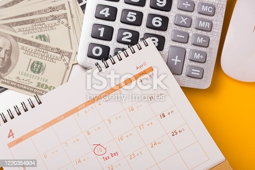 1185240988 istock photo April of the year is Tax Day, Top view flat lay closeup calculator, laptop computer, calendar, and Dollar money, on yellow background business finance budget concept with copy space for text 1220354934