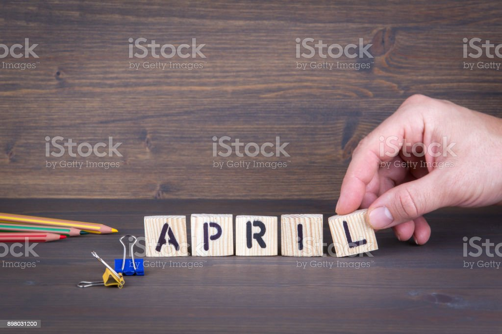 april. Wooden letters on the office desk, informative and communication background stock photo