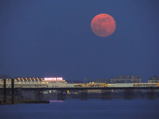 April's Pink Full Moon Over Palace Pier, Brighton stock photo
