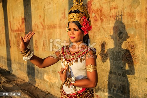 A woman shows Apsara dance in old ruins near Siem Reap, Cambodia.