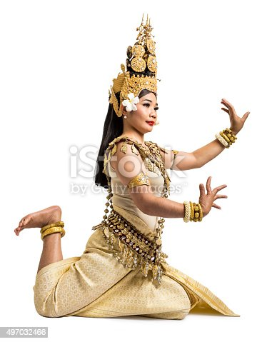 A traditional Apsara dancer of Cambodia poses gracefully on the floor. Apsara dance is an ancient Khmer tradition dating back to the splendor of Angkor Wat. Studio shot and isolated on a white background.