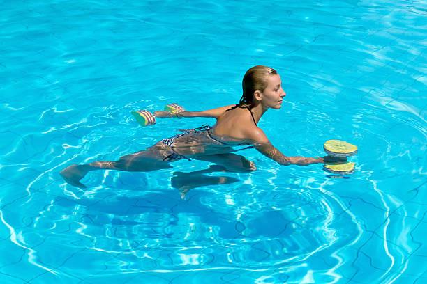 Acqua aerobica in acqua, donna con manubri - foto stock