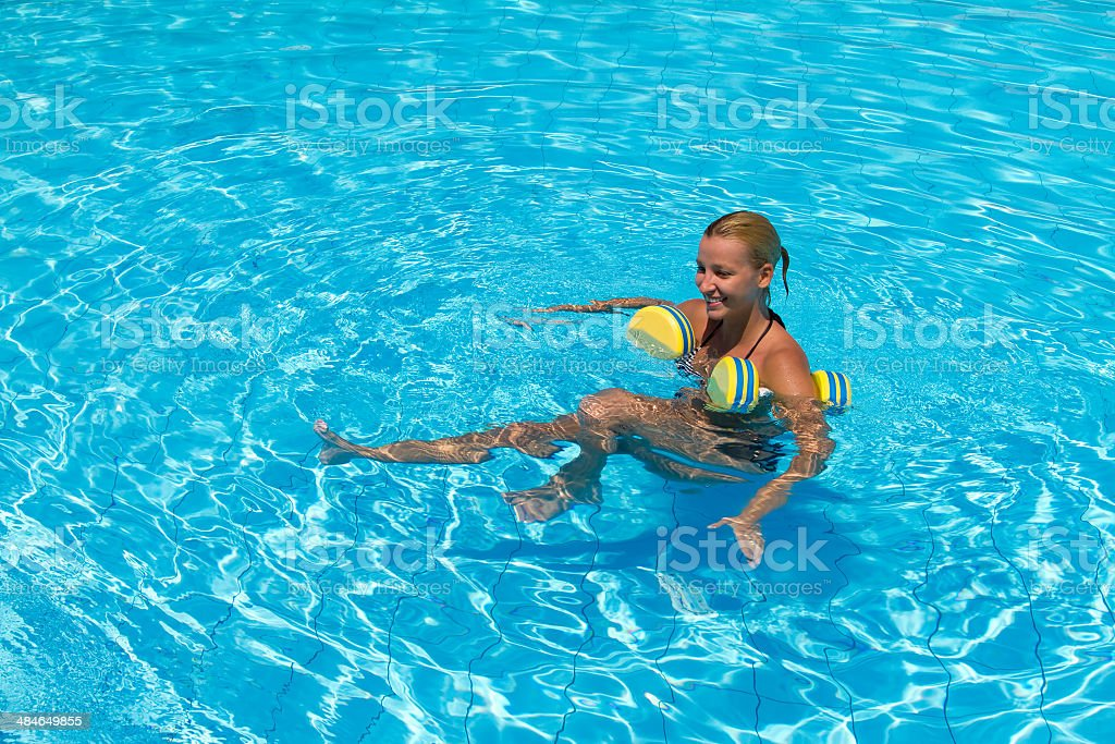 Aqua aerobic, woman in water with dumbbells stock photo