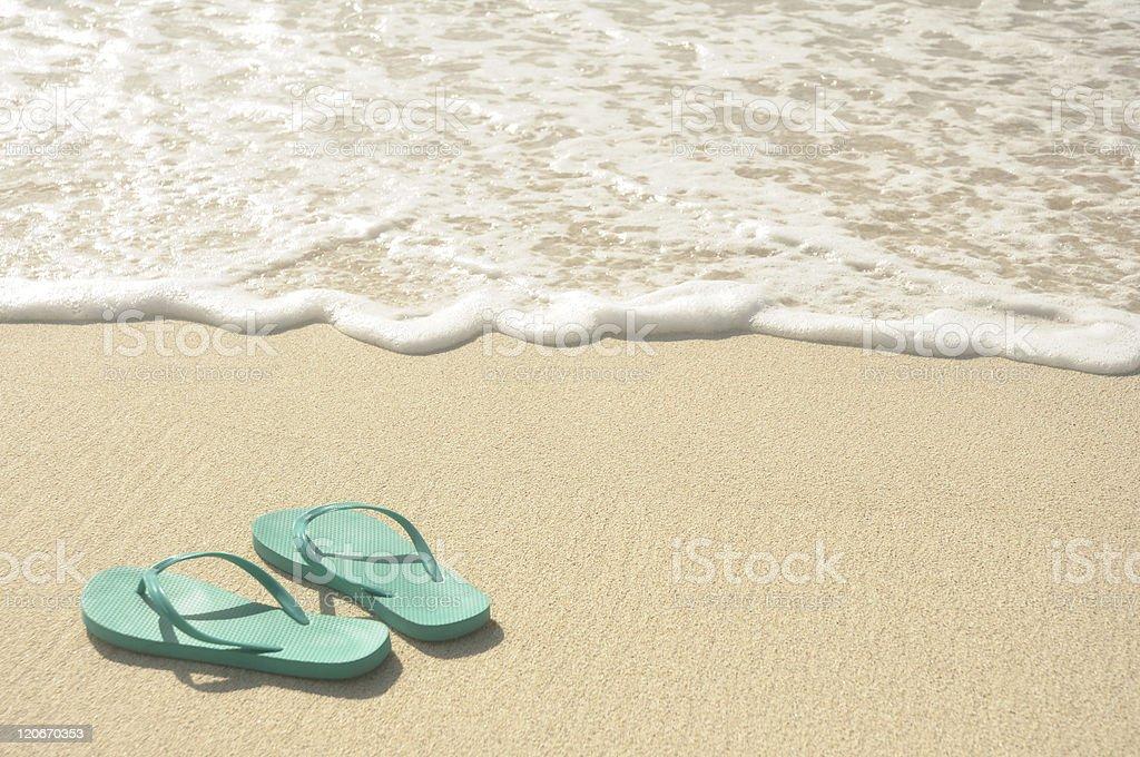 Aqua blue flip flops in the sand near the waves stock photo
