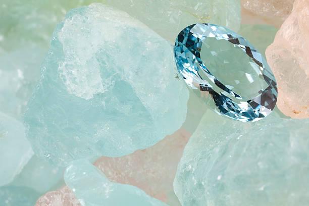 Aquamarine Gems(XXXL) Polished aquamarine is on rough aquamarine gems. gemstone stock pictures, royalty-free photos & images
