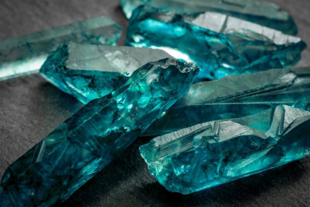 Aquamarines  and raw crystal gems Aquamarines  and raw crystal gems concept with closeup of a bunch of blue uncut aquamarine, topaz or tourmaline crystals gemstone stock pictures, royalty-free photos & images
