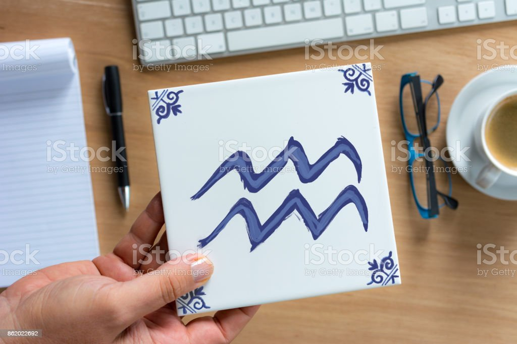 aquarius Delfts Blue zodiac tile above working desk stock photo