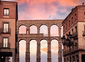 Aqueduct of Segovia and typical architecture in the historic center of the city, during a sunset of reddish and bluish tones