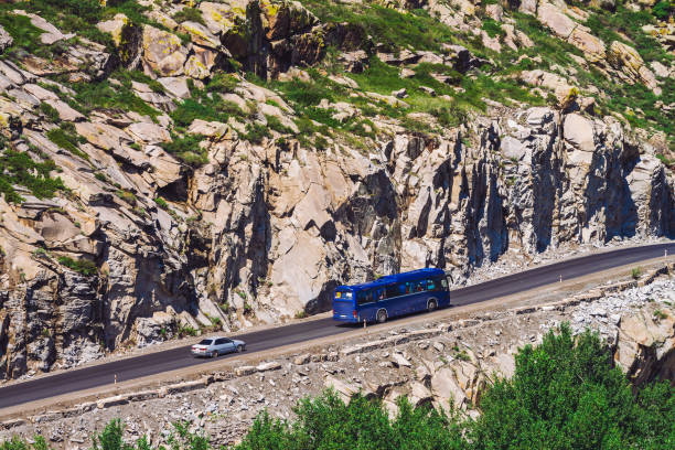 ð¡ar drives along highland highway over abyss near giant rocky cliff. amazing highlands road on pass. tourists in bus. trip in mountains. mountain tourism. - altai nature reserve стоковые фото и изображения