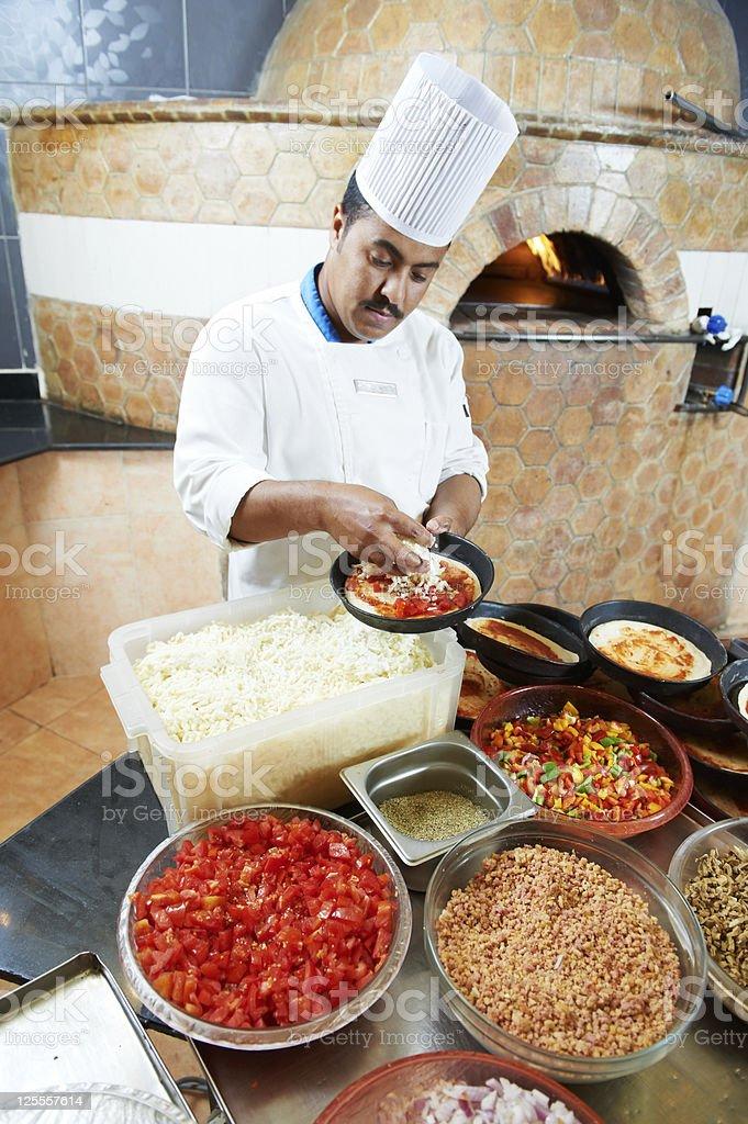 Arab baker chef making Pizza royalty-free stock photo