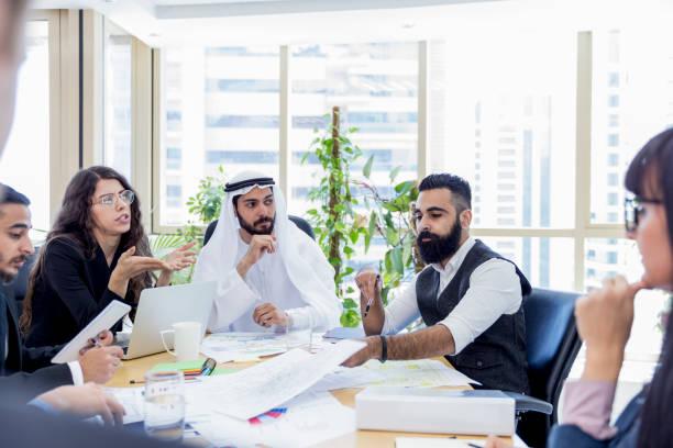 arab business executive chairing an important business meeting - arab стоковые фото и изображения