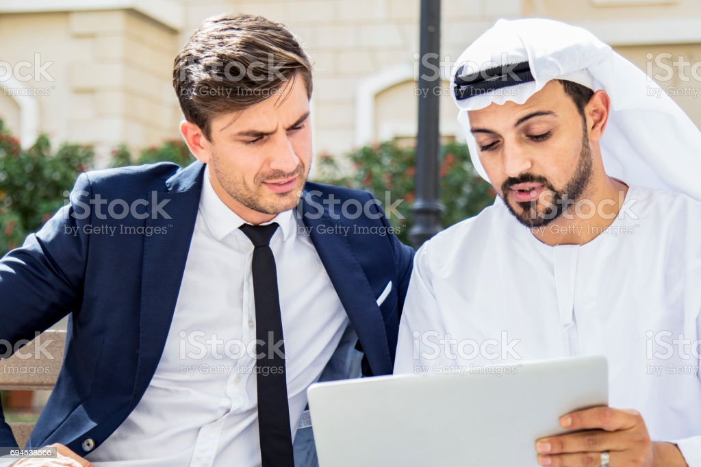 Arab business executive showing his business model using digital tablet stock photo