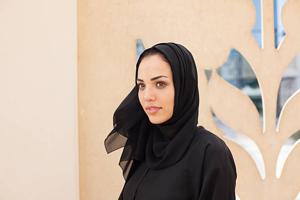 Arab business woman in front of traditional architectural detail Arab business woman of traditional architectural details. She is wearing an Abaya and Hijab, the traditional national dress of the United Arab Emirates, Saudi Arabia, Kuwait, Bahrain, Iraq, Oman, Qatar and Yemen. Image is taken during Dubai Istockalypse in UAE religious veil stock pictures, royalty-free photos & images