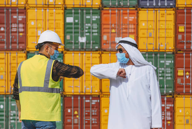 Arab Businessman and Engineer with face masks greeting each other by elbow bumping on a large commercial dock during pandemic stock photo