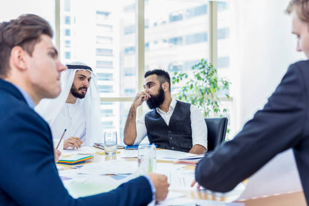 Arab businessman chairing a business meeting, while talking to his associate stock photo