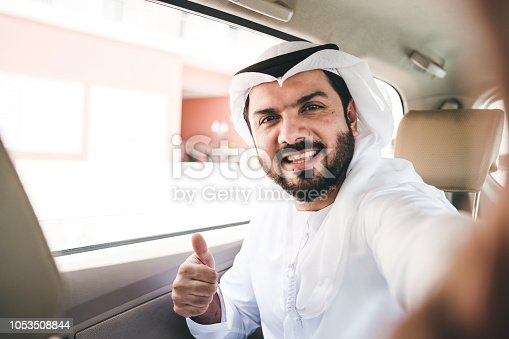 491496340 istock photo Arab businessman doing a selfie inside a taxi 1053508844