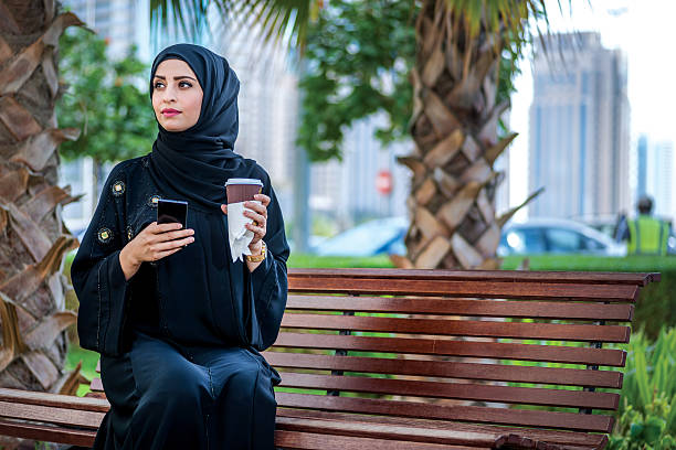 arab businessman holding a coffee wearing the hijab - saudi woman stock photos and pictures