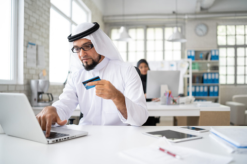 istock Arab businessman in modern office shopping with credit card 1008791710