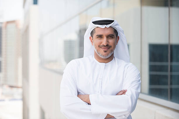 Arab businessman portrait outside office building A photo of confident and smiling mid adult arab businessman. Emirati man is wearing tradition clothing. Portrait of middle eastern professional standing arms with crossed outside office building. Dubai, United Arab Emirates, Middle East arabia stock pictures, royalty-free photos & images