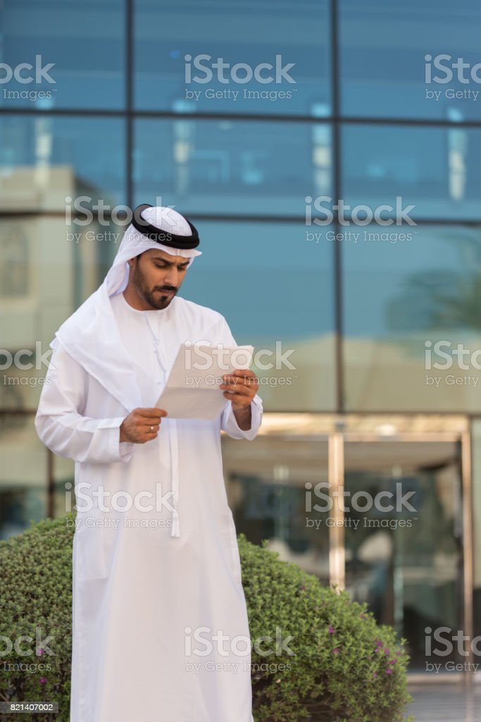 Arab Businessman Reviewing Document Outside Modern Office Building, Dubai stock photo