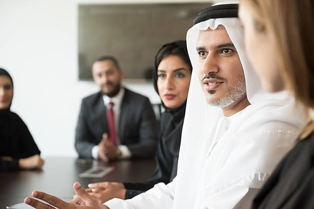 Arab businessman talking in a meeting A photo of serious Arab businessman communicating in a meeting. Emirati man is wearing traditional thobe. Middle Eastern professional is discussing while sitting with colleagues, Coworkers are listening to him, in brightly lit office. arabia stock pictures, royalty-free photos & images