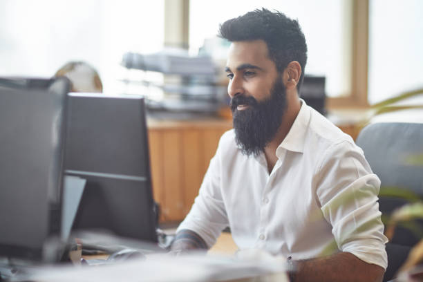 Arab businessman using computer at desk stock photo