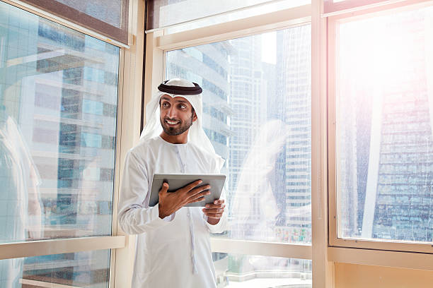 Arab businessman using digital tablet in Dubai office. Arab businessman using digital tablet in Dubai office. Shoot from Istockalypse Dubai 2015. Arabia stock pictures, royalty-free photos & images