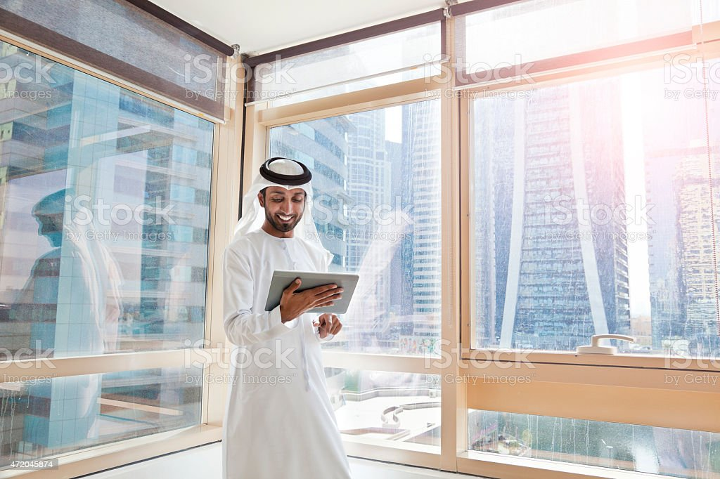 Arab businessman using digital tablet in Dubai office stock photo