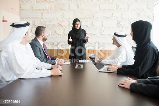 A photo of young and smiling Arab businesswoman gesturing while giving presentation. Emirati business people are wearing traditional clothes of those and abaya. Multi-ethnic colleagues are listening to her very carefully. All are in brightly lit office.