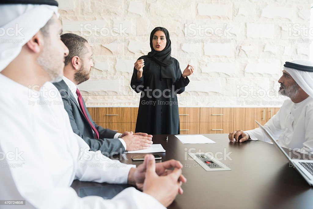 Arab businesswoman giving presentation to coworkers in office stock photo