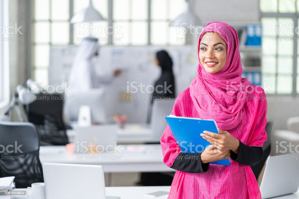 Arab businesswoman standing in modern workplace, holding documents.