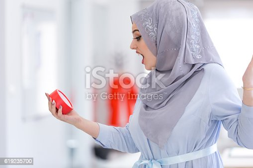 istock Arab Businesswoman with clock being late wearing hijab 619235700