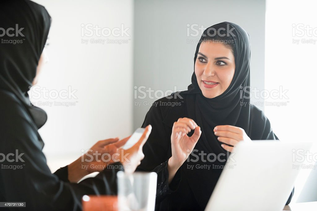 Arab businesswomen in traditional clothes discussing in office stock photo