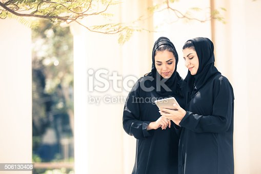 Two Emirati women having a conversation with their digital tablet in a park. Image taken during iStockalypse 2015, Dubai, United Arab Emirates