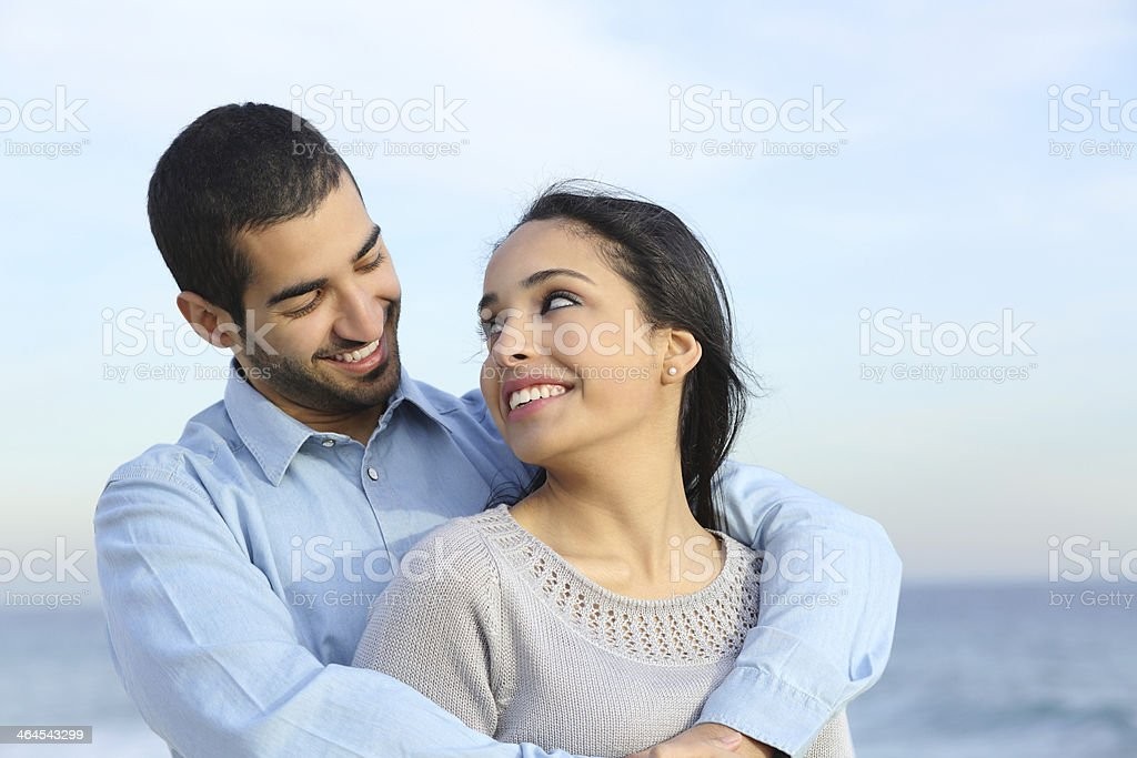 Arab casual couple cuddling happy with love on the beach stock photo