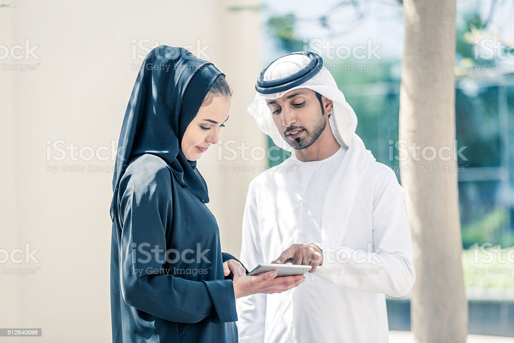 Arab Couple in a Park with Digital Tablet stock photo