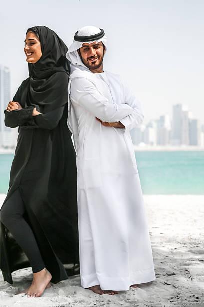 arabische paar in traditioneller kleidung am strand  - hochzeitsreise dubai stock-fotos und bilder