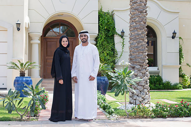 Arab family portrait in front of their house Middle Eastern couple standing in front of their house on a sunny day, both wearing the traditional Emirati dresses . arabia stock pictures, royalty-free photos & images